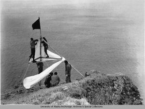 Six men putting up a survey point and flag on Kiska Island.